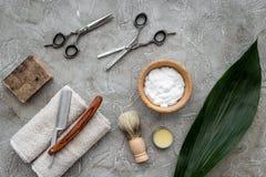 Accesorios para afeitar Brocha de afeitar, maquinilla de afeitar, espuma, sciccors en la opinión superior del fondo de piedra gri Imágenes de archivo libres de regalías