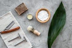 Accesorios para afeitar Brocha de afeitar, maquinilla de afeitar, espuma, sciccors en la opinión superior del fondo de piedra gri Fotografía de archivo