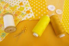Accesorios para coser en amarillo-blanco Imagenes de archivo