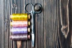 Accesorios para coser en la tabla de madera oscura Foto de archivo