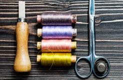 Accesorios para coser en la tabla de madera oscura Imagen de archivo libre de regalías