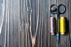 Accesorios para coser en la tabla de madera oscura Foto de archivo libre de regalías