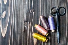 Accesorios para coser en la tabla de madera oscura Imagen de archivo