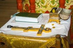 Accesorios para el bautizo de los iconos de los niños de las velas y de la fuente, cruz, tijeras, biblia, la iglesia de Ortodox E imagenes de archivo