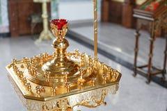 Accesorios para el bautizo de los iconos de los niños de las velas y de la fuente, la iglesia de Ortodox El sacramento de niños Imagen de archivo libre de regalías