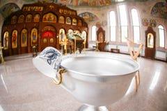 Accesorios para el bautizo de los iconos de los niños de las velas y de la fuente, la iglesia de Ortodox El sacramento de niños Fotos de archivo