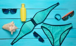 Accesorios para el centro turístico en la playa y los artilugios en un fondo de madera azul Traje de baño, pulsera elegante, sunb Foto de archivo libre de regalías