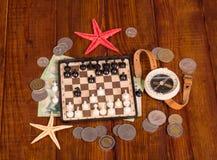 Accesorios para el viajero: ajedrez, compás y dinero en la madera oscura Imágenes de archivo libres de regalías