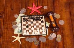 Accesorios para el viajero: ajedrez, dinero del reloj de arena contra la madera oscura Imagenes de archivo