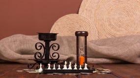 Accesorios para el viajero: ajedrez, dinero del reloj de arena y palmatoria en marrón Imagen de archivo