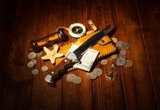 Accesorios para el viajero: compás, reloj de arena, cuchillo, dinero en la madera oscura Imagen de archivo