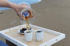 Accesorios para la alternativa que prepara el café en una bandeja en la playa arenosa Barista derrama el café en las tazas Imagenes de archivo