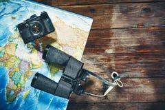 Accesorios para la cámara, el mapa y los prismáticos de la película del vintage del viaje en la tabla de madera, visión superior  Fotografía de archivo libre de regalías