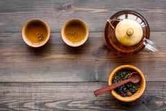 Accesorios para la ceremonia de té Pote del té, tazas, hojas de té secas en copyspace de madera oscuro de la opinión superior del Imágenes de archivo libres de regalías