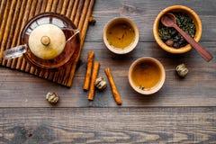 Accesorios para la ceremonia de té Pote del té, tazas, hojas de té secas en copyspace de madera oscuro de la opinión superior del Fotos de archivo