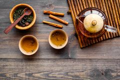 Accesorios para la ceremonia de té Pote del té, tazas, hojas de té secas en copyspace de madera oscuro de la opinión superior del Imagen de archivo