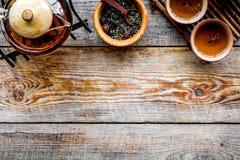 Accesorios para la ceremonia de té Pote del té, tazas, hojas de té secas en copyspace de madera rústico de la opinión superior de Fotos de archivo