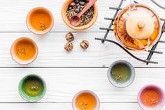 Accesorios para la ceremonia de té Pote del té, tazas, hojas de té secas en el copyspace de madera blanco de la opinión superior  Imágenes de archivo libres de regalías