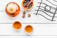 Accesorios para la ceremonia de té Pote del té, tazas, hojas de té secas en el copyspace de madera blanco de la opinión superior  Fotos de archivo libres de regalías
