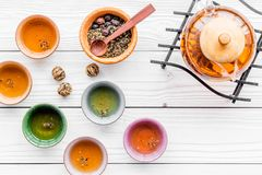 Accesorios para la ceremonia de té Pote del té, tazas, hojas de té secas en el copyspace de madera blanco de la opinión superior  Imagenes de archivo