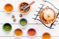 Accesorios para la ceremonia de té Pote del té, tazas, hojas de té secas en la opinión superior del fondo de madera blanco Foto de archivo libre de regalías