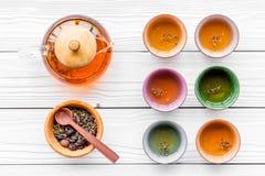 Accesorios para la ceremonia de té Pote del té, tazas, hojas de té secas en la opinión superior del fondo de madera blanco Fotos de archivo libres de regalías