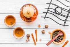 Accesorios para la ceremonia de té Pote del té, tazas, hojas de té secas en la opinión superior del fondo de madera blanco Foto de archivo