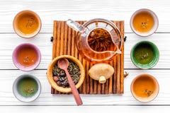 Accesorios para la ceremonia de té Pote del té, tazas, hojas de té secas en la opinión superior del fondo de madera blanco Fotografía de archivo libre de regalías