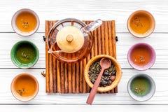 Accesorios para la ceremonia de té Pote del té, tazas, hojas de té secas en la opinión superior del fondo de madera blanco Imagen de archivo