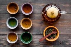 Accesorios para la ceremonia de té Pote del té, tazas, hojas de té secas en la opinión superior del fondo de madera oscuro Foto de archivo libre de regalías
