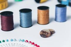 Accesorios para la costura en el fondo blanco del paño Fotografía de archivo