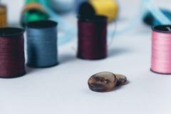 Accesorios para la costura en el fondo blanco del paño Imagenes de archivo