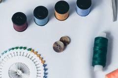 Accesorios para la costura en el fondo blanco del paño Foto de archivo libre de regalías