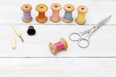 Accesorios para la costura hecha a mano en el fondo de madera blanco Fotografía de archivo
