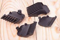 Accesorios para las podadoras de pelo en una tabla de madera ligera Fotografía de archivo libre de regalías