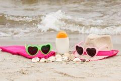 Accesorios para las vacaciones en la arena en la playa, protección del sol en concepto del tiempo de verano Fotos de archivo