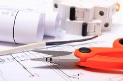 Accesorios para los trabajos del ingeniero y rollos de diagramas en el dibujo de construcción Fotos de archivo libres de regalías