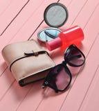 Accesorios para mujer en un fondo de madera rosado Espejo, gafas de sol, monedero, botella de perfume Foto de archivo