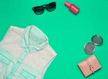 Accesorios para mujer y ropa en un fondo de la turquesa Camisa de los vaqueros, espejo, botella de perfume, gafas de sol, moneder Fotos de archivo libres de regalías
