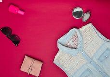 Accesorios para mujer y ropa en un fondo rojo Camisa de los vaqueros, espejo, botella de perfume, gafas de sol, monedero Copie el Imágenes de archivo libres de regalías