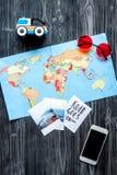 Accesorios para treveling con los niños, el teléfono, el mapa y las fotos en maqueta oscura de la opinión superior del fondo del  Fotos de archivo libres de regalías