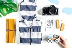 Accesorios para treveling con los niños, la cámara y el traje en la opinión superior del fondo blanco Fotos de archivo libres de regalías