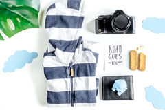 Accesorios para treveling con los niños, la cámara y el traje en la opinión superior del fondo blanco Fotografía de archivo