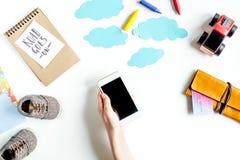 Accesorios para treveling con los niños y el teléfono móvil en la maqueta blanca de la opinión superior del fondo Fotos de archivo libres de regalías