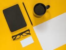 Accesorios planos del negocio del negro de la endecha en fondo amarillo con el bl Foto de archivo