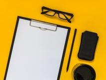 Accesorios planos del negocio del negro de la endecha en fondo amarillo con el bl Imágenes de archivo libres de regalías