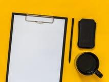 Accesorios planos del negocio del negro de la endecha en fondo amarillo con el bl Fotografía de archivo