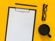 Accesorios planos del negocio del negro de la endecha en fondo amarillo con el bl Imagenes de archivo