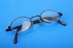 Accesorios retros del hombre - vidrios viejos en un fondo de cuero azul Foto de archivo