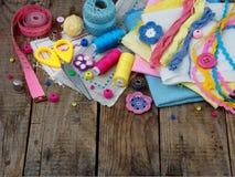 Accesorios rosados, amarillos y azules para la costura en fondo de madera El hacer punto, bordado, cosiendo Pequeña empresa Renta Fotos de archivo libres de regalías